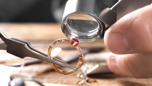 Inspecting ring with gem through a loupe